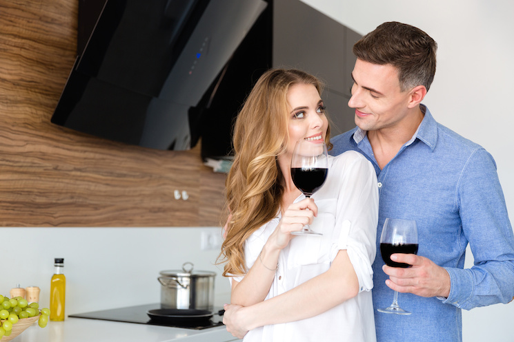 Happy couple drinking red wine and flirting at home