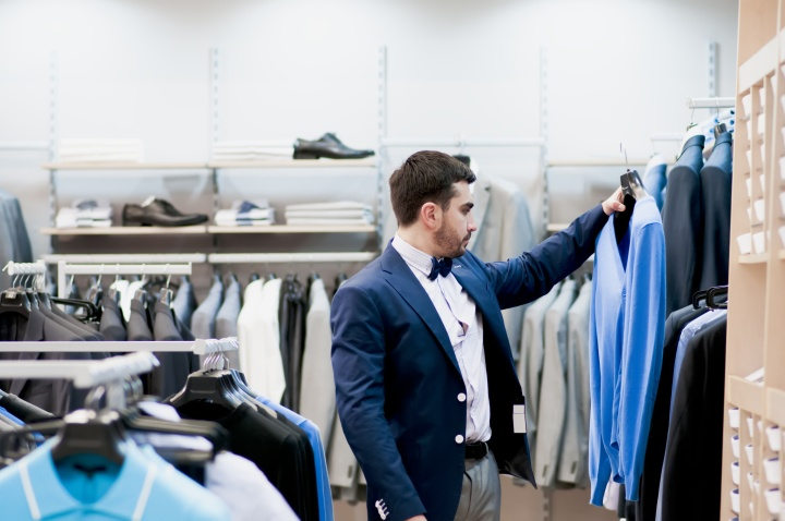 Attractive young  man buying a tee-shirt at a boutique.