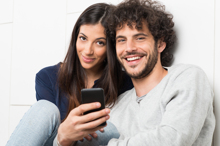 Happy Couple Holding Cellphone